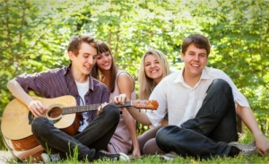 a group of teens sitting on the grass