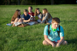 lonely teenager sitting away from group